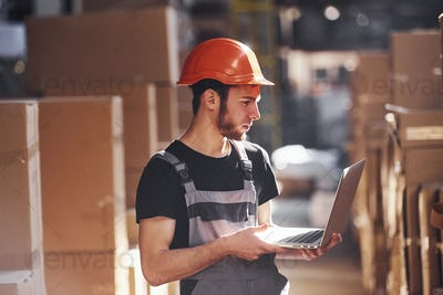 Storage worker in uniform and modern laptop in hands checks production