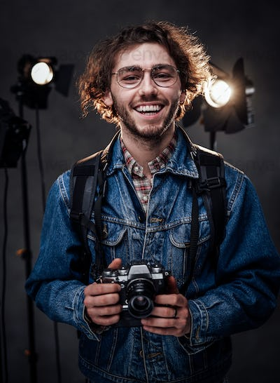 Young photographer holds a camera. Studio portrait with lighting equipment in the background