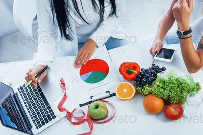 Top view of female nutritionist that gives consultation to patient indoors in the office