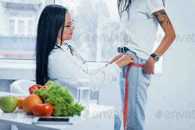 Female nutritionist measuring waist of patient by tape indoors in the office