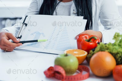 Female nutritionist sitting indoors in the office at workplace and showing information on document