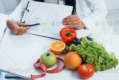 Female nutritionist indoors in the office at workplace and showing information on document