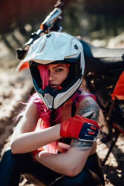 Beautiful hipster girl with a tattoo on his arm and pink hair covering the eye in safety helmet