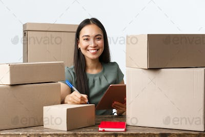 Small business owners, startup and e-commerce concept. Smiling successful asian businesswoman with