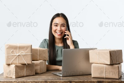 Small business owners, startup and e-commerce concept. Smiling asian businesswoman talking with