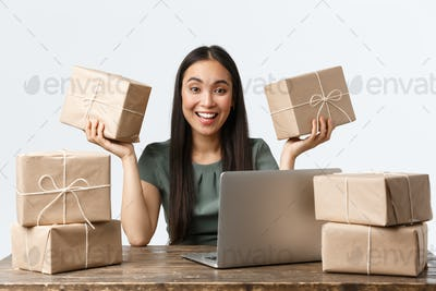 Small business owners, startup and e-commerce concept. Excited asian female entrepreneur sitting at