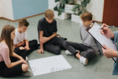 Group of teenagers sit in a circle on the floor and prepare a project together