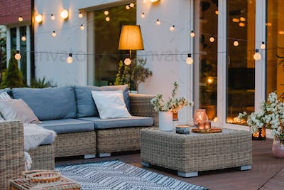 Summer with patio with wicker furniture and lights