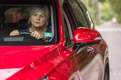 Old lady behind the wheel of a luxury red car