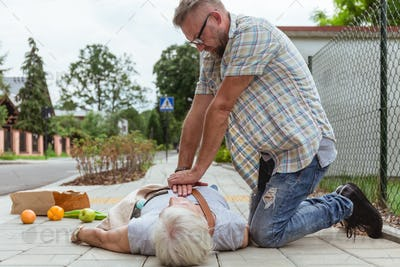 Man performs a heart massage on an senior lady who fainted on the street