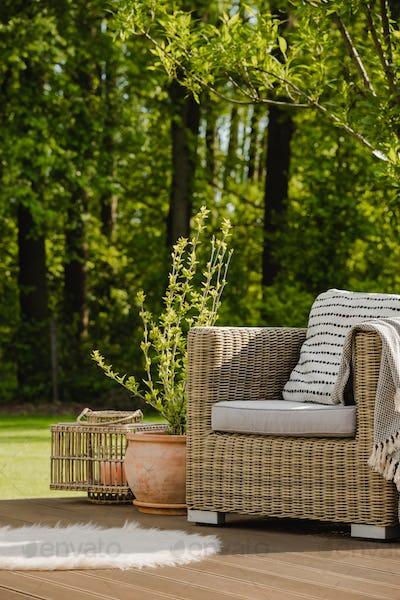 Wicker armchair with pillow on green terrace in beautiful garden