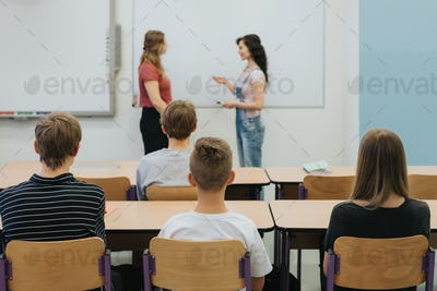Young teacher and students in the classroom during the lesson