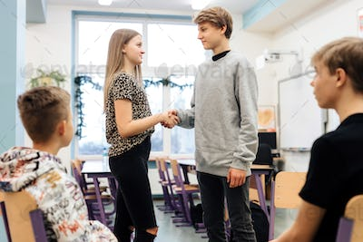 Two friends at odds shake hands during a workshop with a psychologist at school