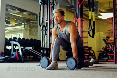 Image of full body athletic male doing squats with dumbbells in a gym club.