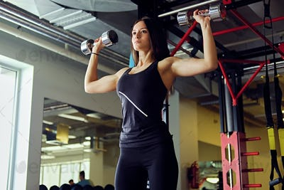 Athletic brunette female holds dumbbells.