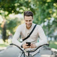 Social networks outdoors. Smiling attractive guy sits on bicycle in park and looks at smartphone