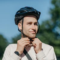 Preparation for ride to bicycle in city. Handsome young man in shirt puts on safety helmet