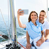 Spouses On Cruise Yacht Making Selfie Standing On Deck Outside