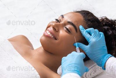 Smiling black woman having anti-aging injection for eye zone