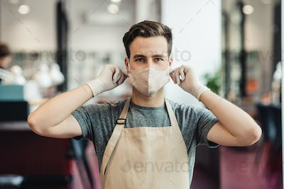 Young man barber putting on protective mask at barbershop