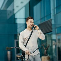 Businessman with urban transport. Portrait of man with phone, near a modern office building