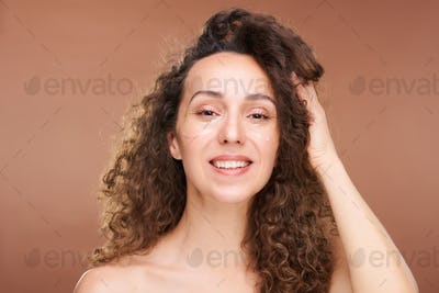 Young happy brunette woman with undereye patches touching long wavy hair