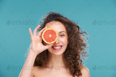 Young cheerful woman with healthy smile and skin looking at you with left eye