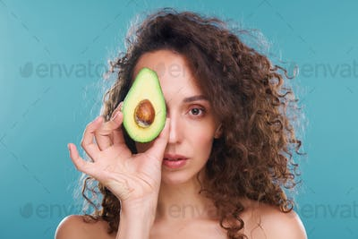 Young woman looking at you with left eye while holding avocado by another one
