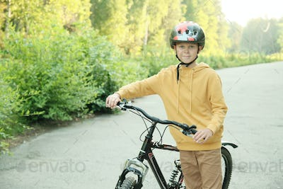 Youthful boy in hoodie, beige pants and protective helmet standing with bicycle