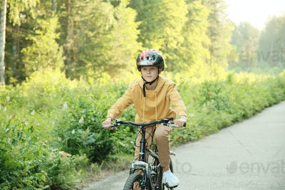 Schoolboy in casualwear and protective helmet riding new bicycle along road