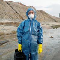 Young female scientist in protective coveralls, rubber gloves and respirator