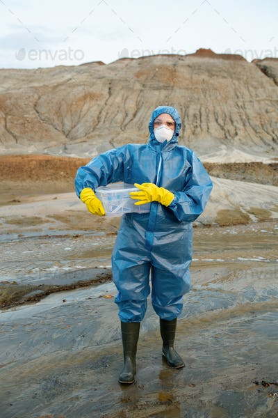 Female scientist in protective coveralls, respirator, rubber gloves and boots