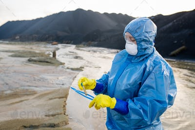Contemporary researcher putting flask with sample of dirty water into packet
