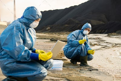 Young female ecologist holding sample of dirty water while looking at colleague
