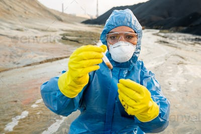 Young female ecologist in respirator and eyeglasses looking at flask with water