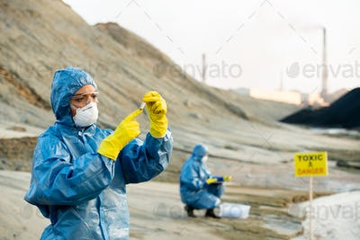 Researcher in protective coveralls looking at sample of toxic soil in hands