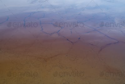 Dirty water with polluted and cracked soil or clay under it on toxic territory