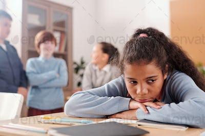Upset or offended schoolgirl sitting by desk against classmates talking