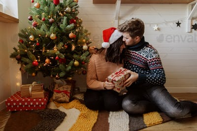 Stylish happy couple exchanging christmas gifts under christmas tree