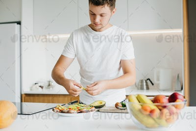 Man putting avocado slices on sandwich made of whole grain bread