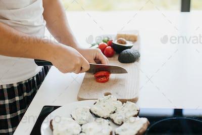 Person cutting tomato slice for sandwich
