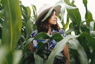 Stylish young woman in blue vintage dress and hat posing in green corn field