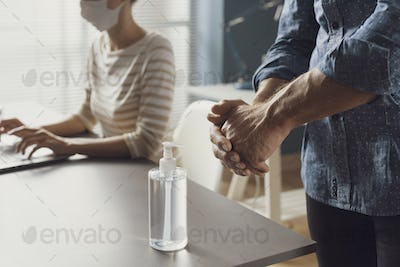 Business people working in the office and applying hand sanitizer on hands
