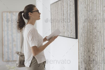 Woman standing in the art gallery and looking at the paintings