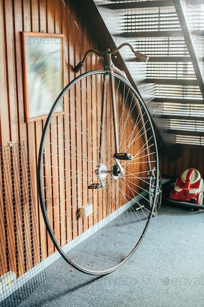 Old fashioned bicycle with one big and one small wheel under the stairs in a house. Selective focus