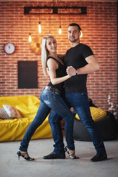 Bachata, merengue, salsa. Two elegance pose on cafe with brick walls