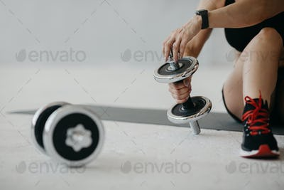 Training for biceps. Adult woman with smartwatch sits on floor at home and adjusts weight of