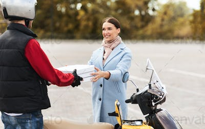 Girl Receiving Order From Pizzeria Standing With Courier Outdoors