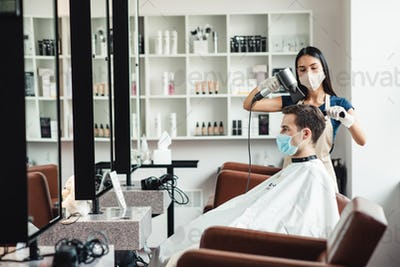 Barber making hairdo for male client, both in medical masks