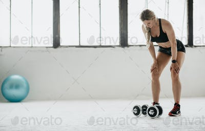 Tired adult woman in sportswear with fitness tracker resting from exercise with dumbbells at